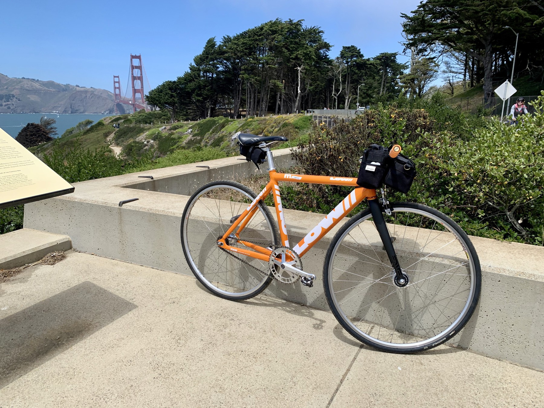 Orange fixed gear bicycle with Golden Gate Bridge in background
