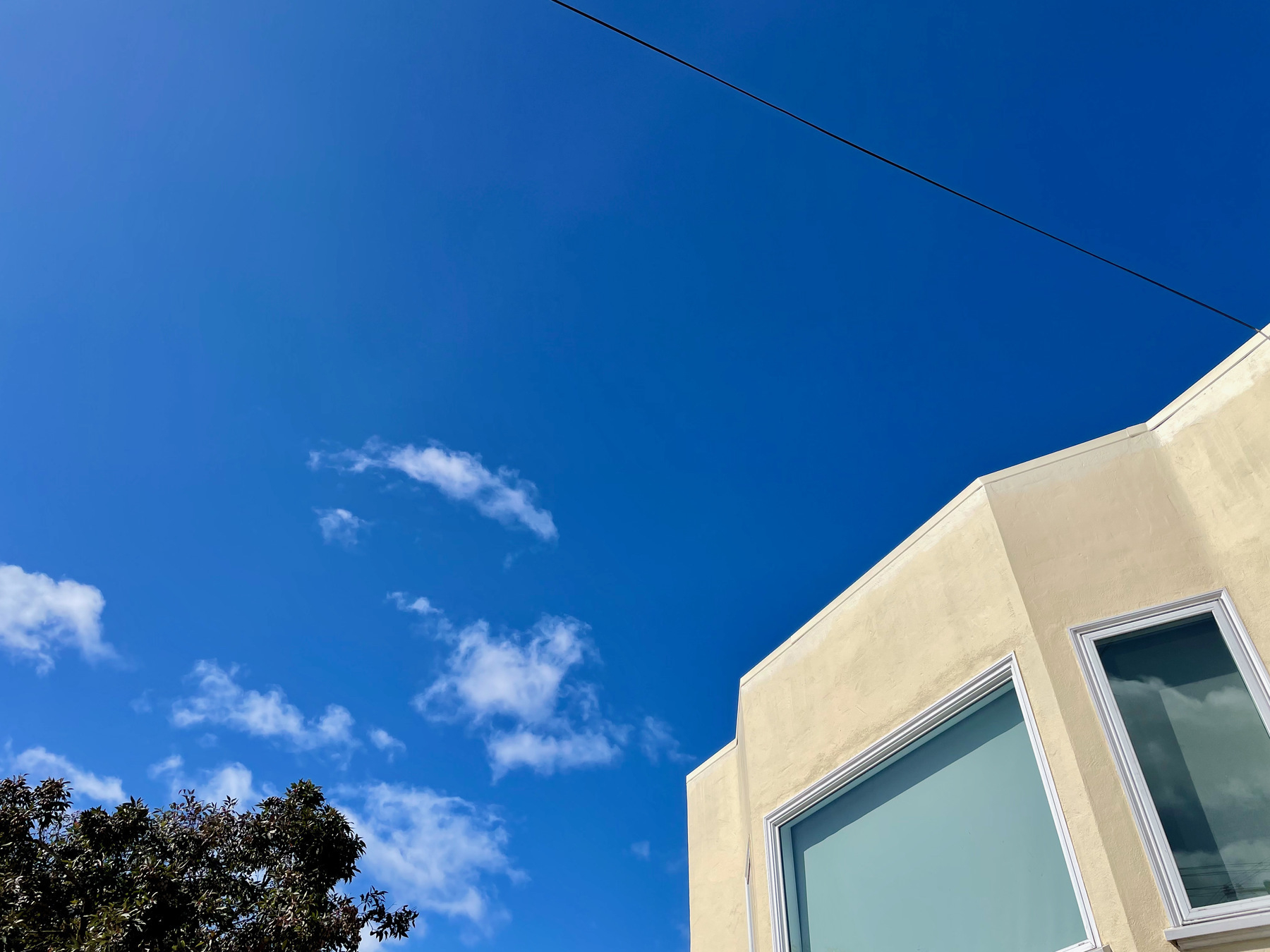 Picture of a few clouds in a blue sky with the top of a gree and the corner of a beige house