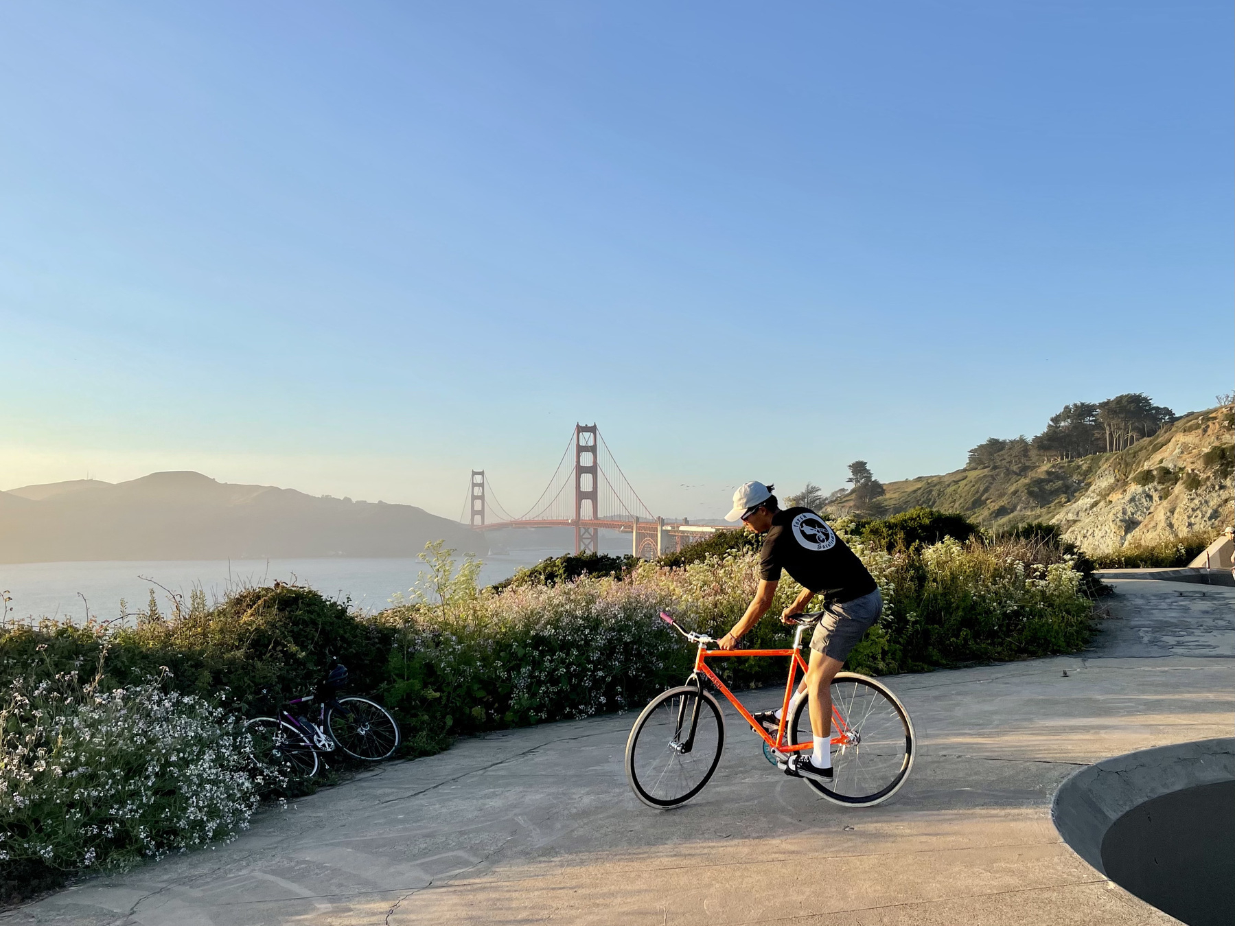 A man on an orange bicycle doing a trick with the Golden Gate Bridge in the background